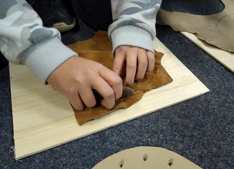 Kinderhände bearbeiten Leder mit Faustkeil auf Holzunterlage